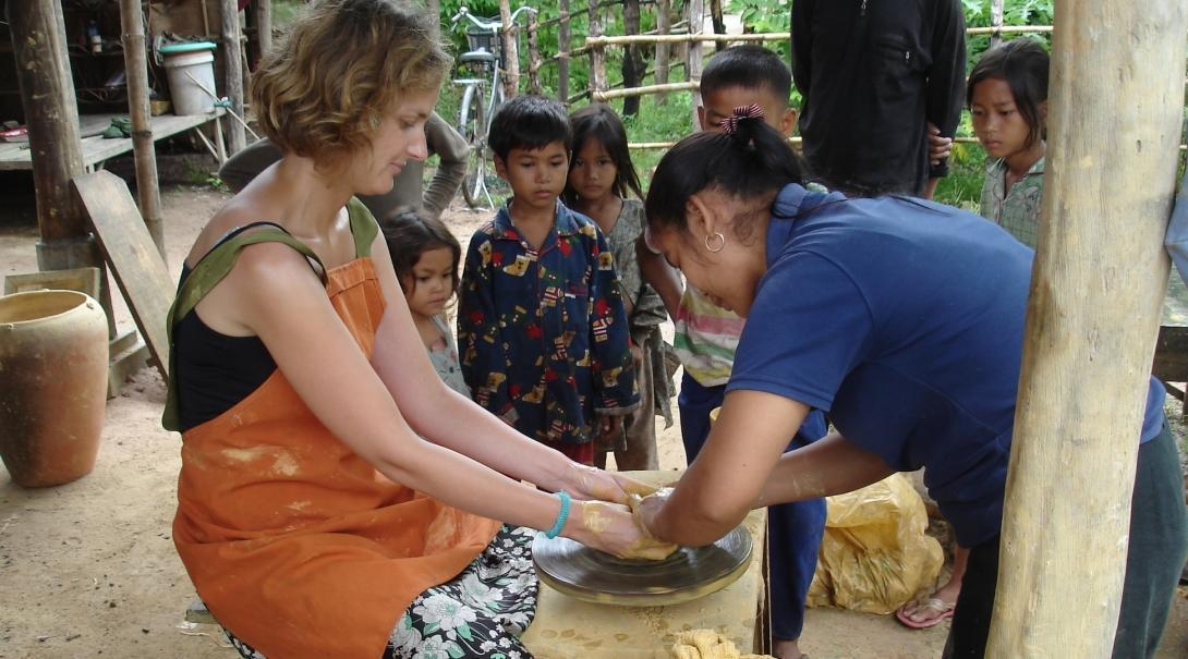 Female Culture and Community Volunteer is taught by local pottery makers how to mould clay during her volunteering placement in Cambodia.